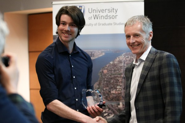 Ian Thomas, biological sciences master's student, accepts his award from University of Windsor President Alan Wildeman, during the Three Minute Thesis competition on Monday, March 26, 2018.