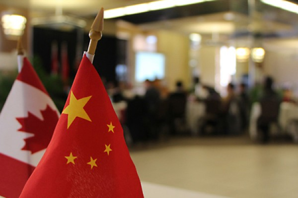 Canadian and Chinese flags adorn conference hall