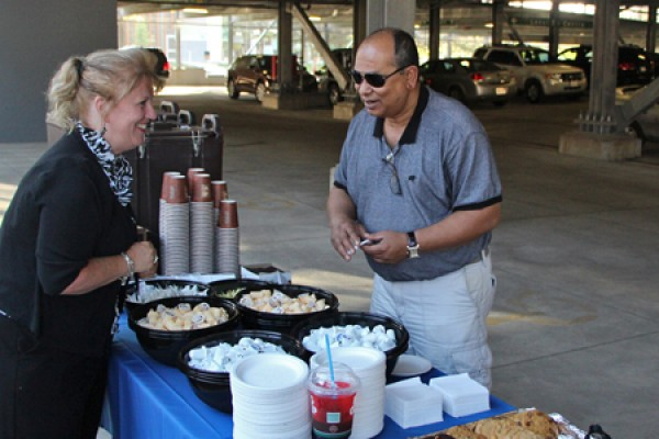 Laurie Butler-Grondin distributes coffee and cookies to a patron of the new campus parking garage.