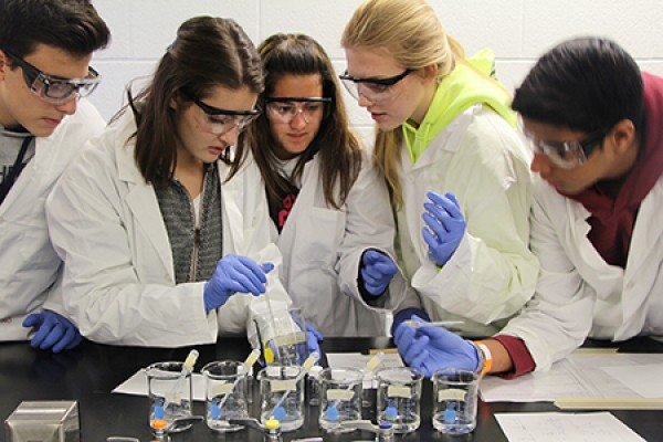 students in lab coats looking over beakers