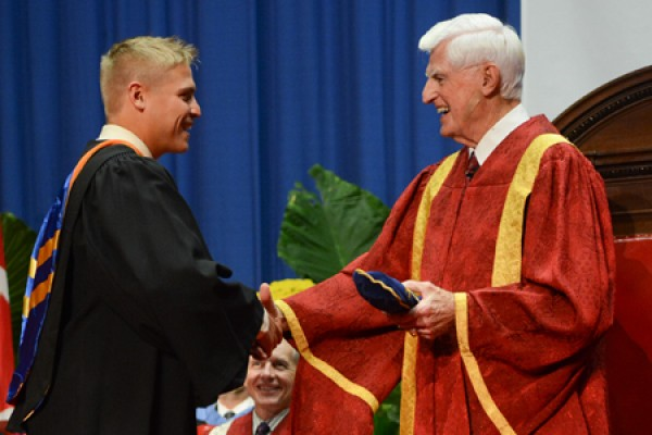 Chancellor Edward Lumley (right) congratulates a new member of the UWindsor alumni family Saturday during the University's 100th Convocation.