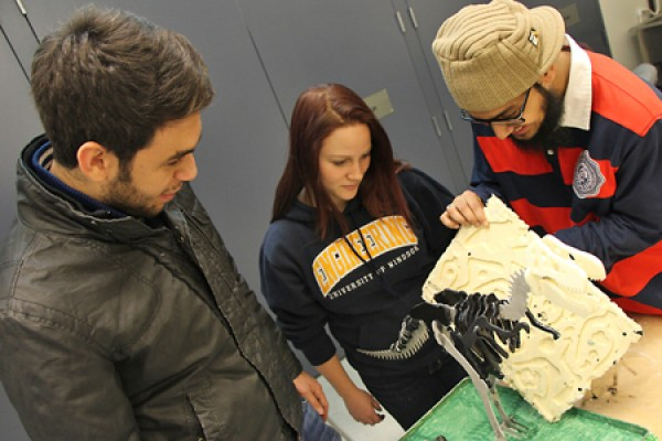 Omar Wasfy, Jordyn McDonald and Usama Saeed look over their model dinosaur
