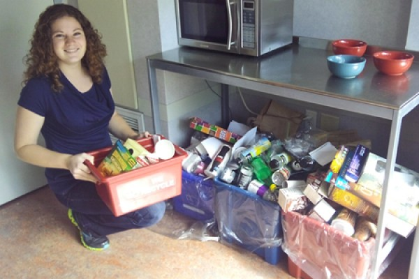 Meghan Riddell empties a container of recyclables