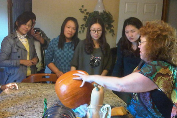 students watch host carve a pumpkin