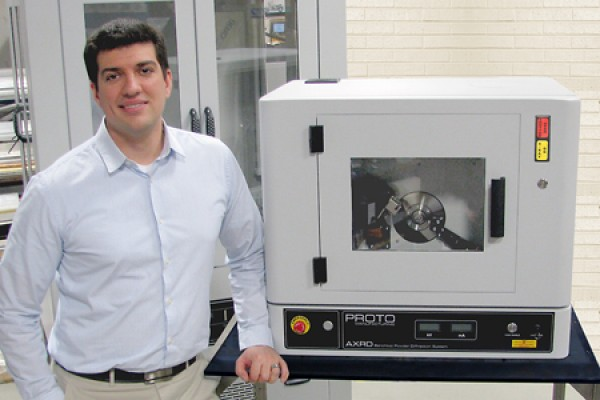 Nick Vukotic poses with PROTO Manufacturing's new benchtop AXRD powder X-ray diffraction system