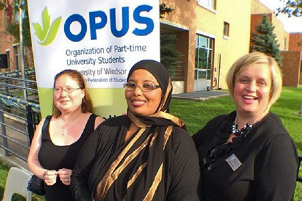 Melissa Woods accepts congratulations from OPUS executive director Maryan Amalow and Patti Lauzo