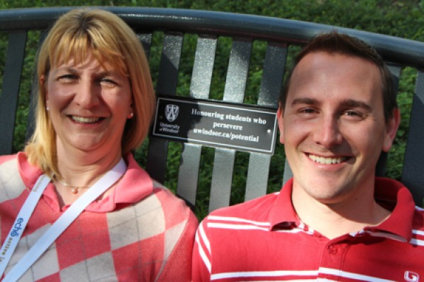 Lorie Stolarchuk and Jonathan Sinasac pose on a bench bearing a plaque promoting a scholarship they set up for students with learning disabilities.