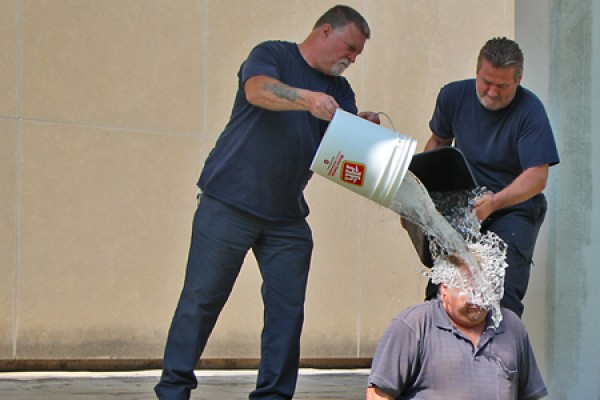 Housekeepers Tom Dean and Colin Bateman pour buckets of ice water over co-worker Mark Spearing