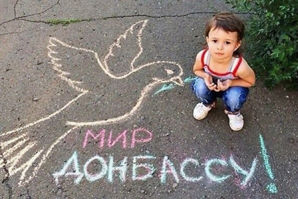 A boy poses next to a chalk drawing expressing the wish for peace for Donbass.
