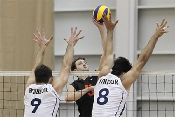 Shawn Reaume and Alexander Vukovic of the Lancer men's volleyball squad jump to block a shot.