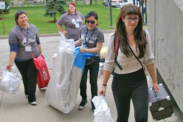 Volunteers help a new student carry her possessions into residence during Move-in Day.