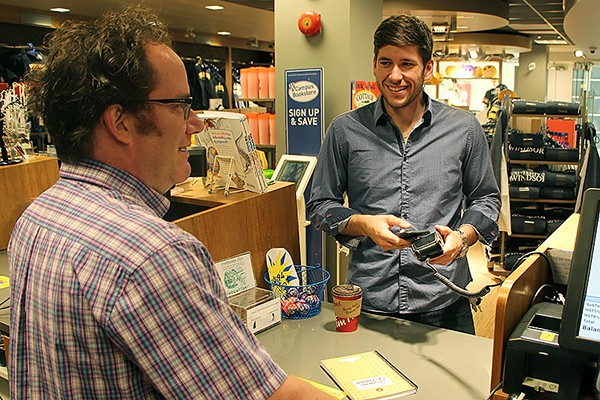Martin Deck of the Campus Bookstore rings through a purchase for student Chris Easby, using his iPhone to pay for it.