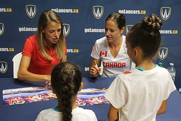 Olympians Melissa Bishop and Noelle Montcalm autograph posters for fans Sienna and Jasmine Benoit.
