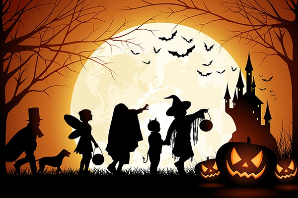 full moon rising behind children in costume