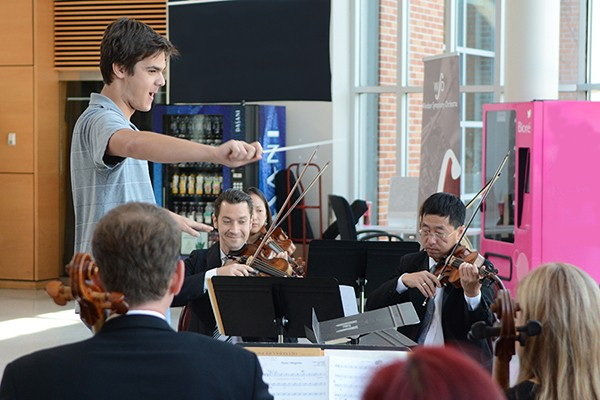 A student conducts musicians of the Windsor Symphony Orchestra.