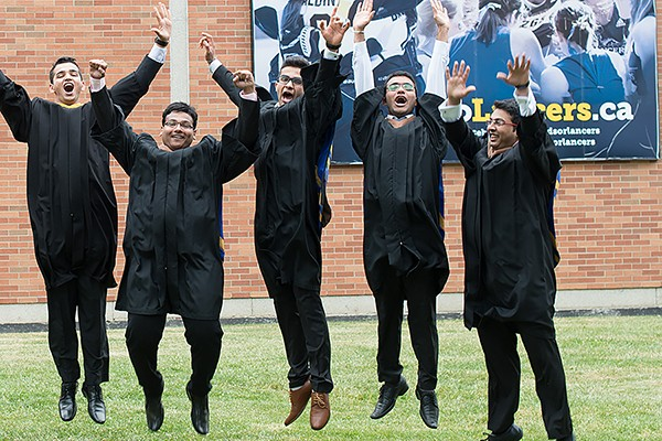 Graduands wearing academic robes jump in the air