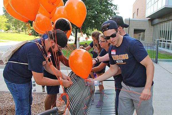 Student volunteers tying balloons to a bench commemorating Jessica Girard