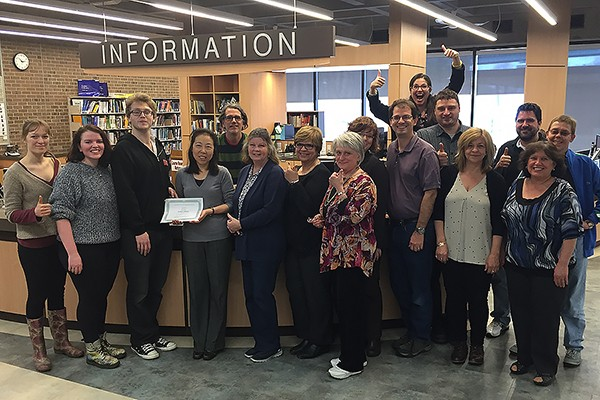 Leddy Library staff are all thumbs-up as Club SODA president Billy Chandler presents them with a certificate of appreciation for their work.