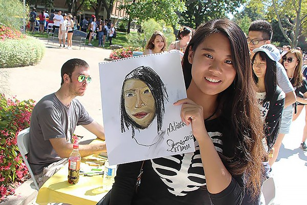 Business major Melissa Li receives a free portrait by artist James Masse during 2015 welcome week activities.