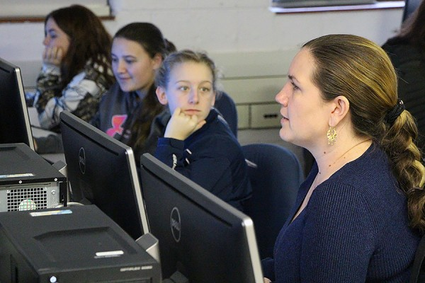 Alice Grgicak-Mannion sitting at computers with students