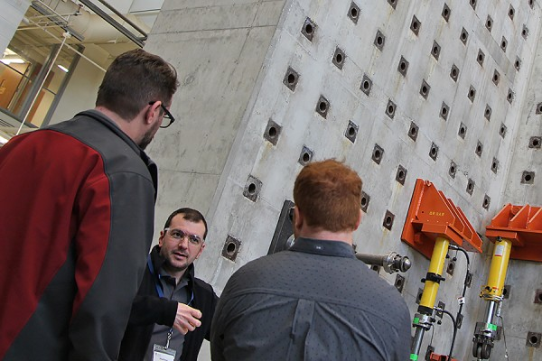 Brian Aldington and Matthew Saby of die set manufacturer Anchor Danly enjoy a tour by grad student John Magliaro of the structural engineering testing lab, Friday in the Centre for Engineering Innovation.