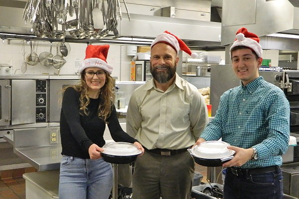 Catering manager Dean Kissner (centre) instructs students Victoria Mahon and Tedi Hoxha in food delivery in preparation for the December 12 ASB lunch service.