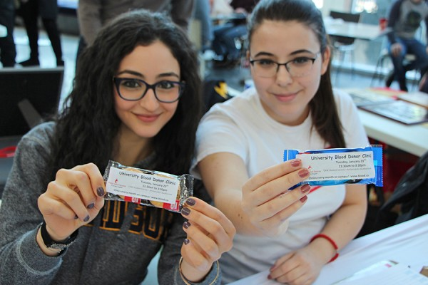 Desiree Mikhael and Milana Milivojevic, volunteers with the UWin Blood Club, display packets of cookies.