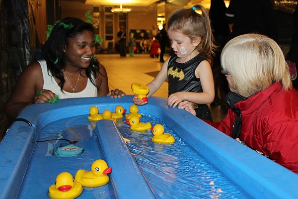 Residence student helps child play duck pond game