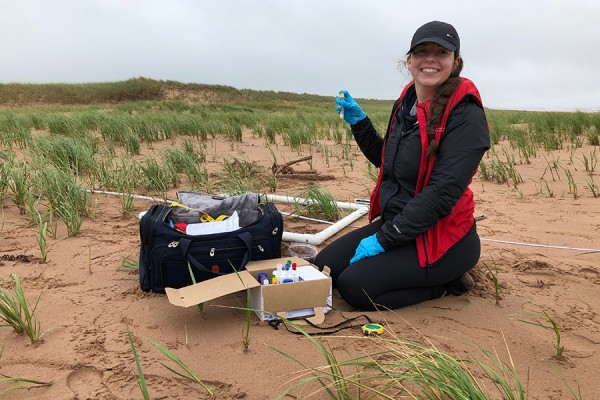 Brianna Lunardi taking samples of the sand and vegetation in Stanhope on the island's north shore.