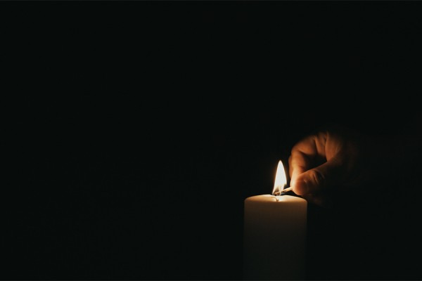 hand lighting single candle in the dark