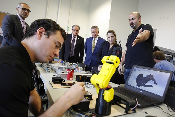 Michael Elachkar, a skilled trades professional enrolled in the university's BEng Tech program, shows Canadian Minister of Foreign Affairs Chrystia Freeland how the class is working with programmable logic controllers to improve industrial automation.