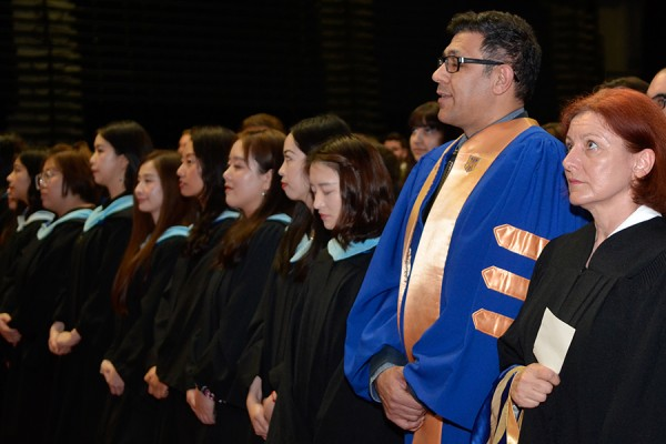 grads in gowns stand during Convocation