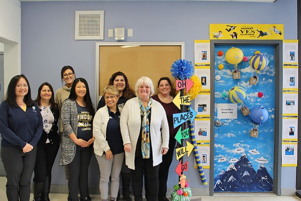 Staff of Co-operative Education and Workplace Partnerships pose with their winning door decorations at the entrance to Room 1100, Lambton Tower.