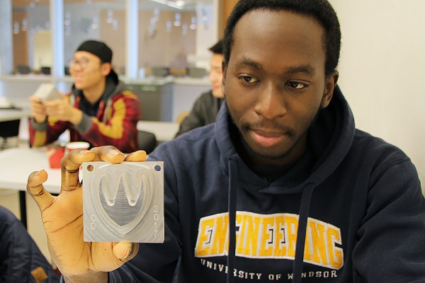 Dimi Olisa shows off the Lancer logo plaque he designed in his third-year CAD/CAM course.