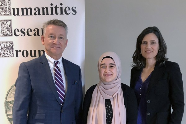 "Last year's ""Why Humanities?"" competition winner, Rima Asfour (centre), accepts congratulations from UWindsor provost Douglas Kneale and Humanities Research Group director Kim Nelson."