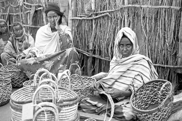 In this photo by Douglas MacLellan, a master basket maker shows her products at the Hagadera Refugee Camp near Dadaab, Kenya.