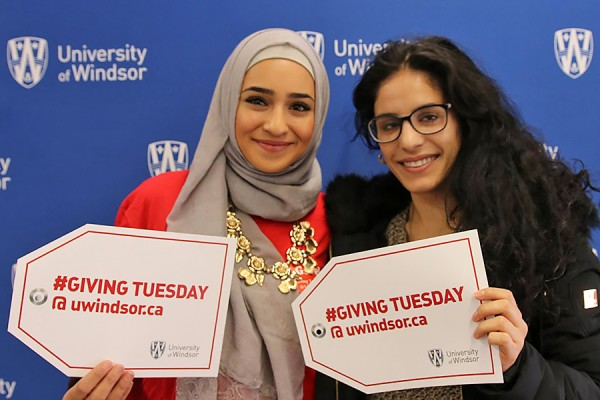 students holding Giving Tuesday signs