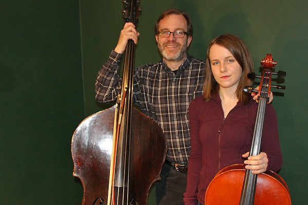 Greg Sheldon holding double bass, daughter Lyra with cello