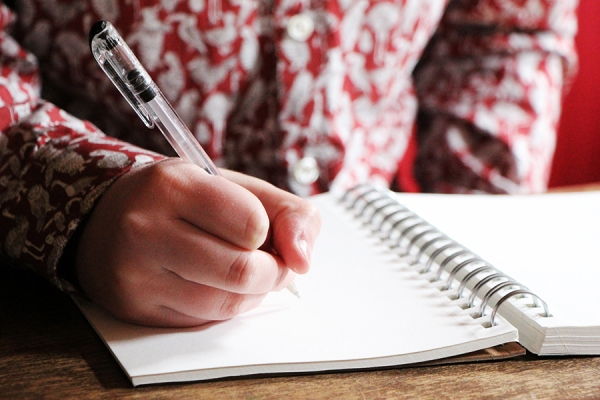 Woman holding pen over creative writing journal.