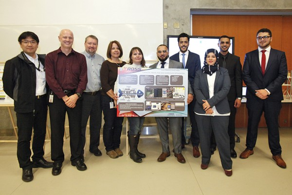Members of a capstone team pose with TRQSS employees at the industrial engineering capstone presentation day, March 31.