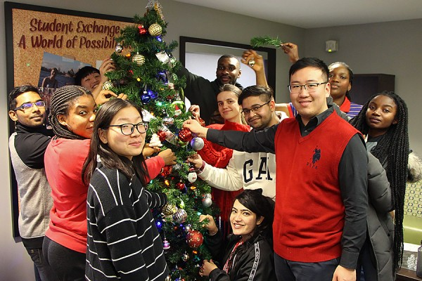 Students from around the world hang ornaments on a tree