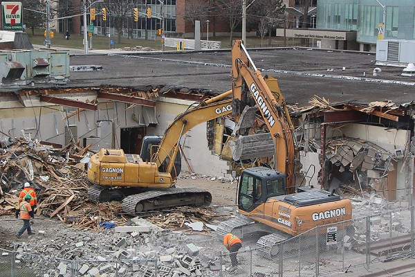 Demolition of the former Music Building advanced Tuesday, with excavators removing exterior and interior walls.