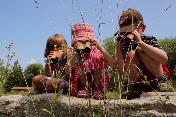 three youngsters looking through binoculars at pond in Ojibway Park