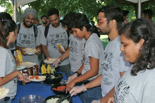 "Wearing ""Part-time and Proud"" T-shirts, volunteers serve diners at the 17th annual barbecue of the Organization of Part-time University Students."