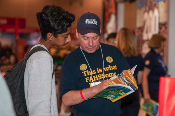 Professor Michael Darroch of the School of Creative Arts promotes its programs to a visitor at the UWindsor booth during the Ontario Universities Fair.