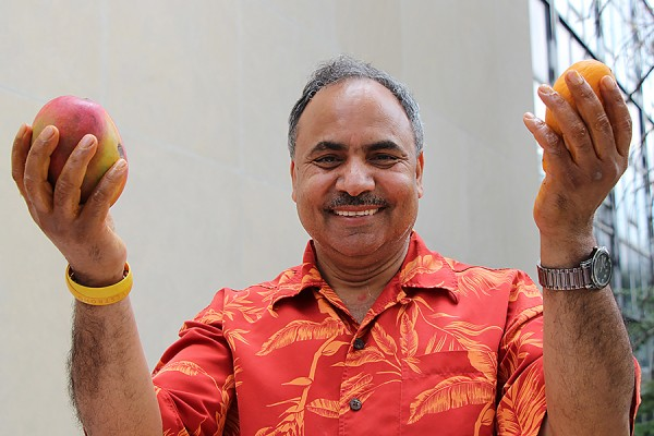 Siyaram Pandey holding up mangoes