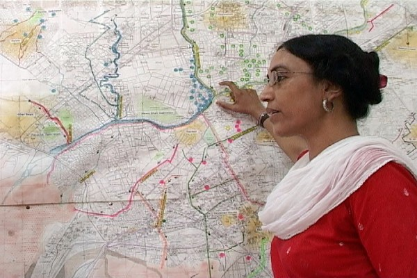 Perween Rahman standing in front of city map
