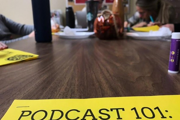 "Group working behind sign that reads ""Podcast 101"""