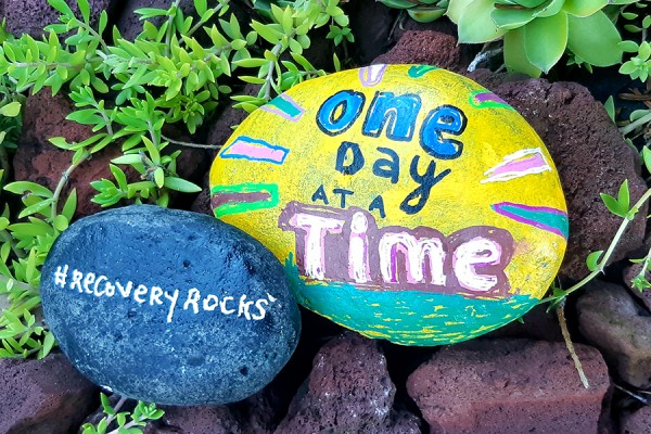 "stone painted with slogan ""One Day at a Time"""
