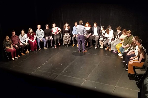 drama students sitting onstage